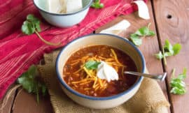 A blue rimmed, white bowl sits on a burlap napkin a top a wood slat table. The bowl is full of the perfect chili, topped with shredded cheese, sour cream and, garnished with cilantro.