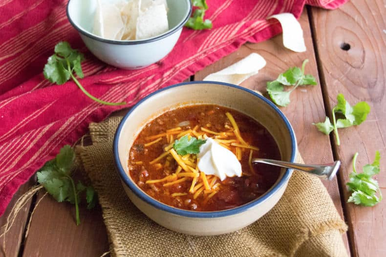 A white, blue rimmed bowl sits on a burlap napkin. The bowl is full of perfect chili, topped with shredded cheese, sour cream and garnished with cilantro.