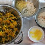 ingredients for dandelion fritters laid out: dandelion flowers, batter, egg, etc.