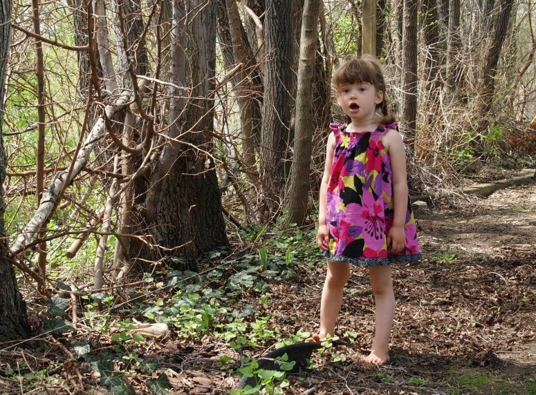 a little girl in a pink flower dress playing barefoot in a forested setting