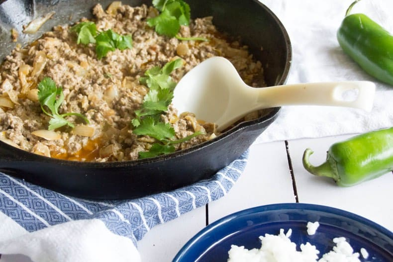 Creamy green chili ground beef in a skillet with rice on the side, and chili peppers beside them