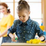 Image of a girl helping to keep the home clean by spraying a counter with cleaner and a cloth.