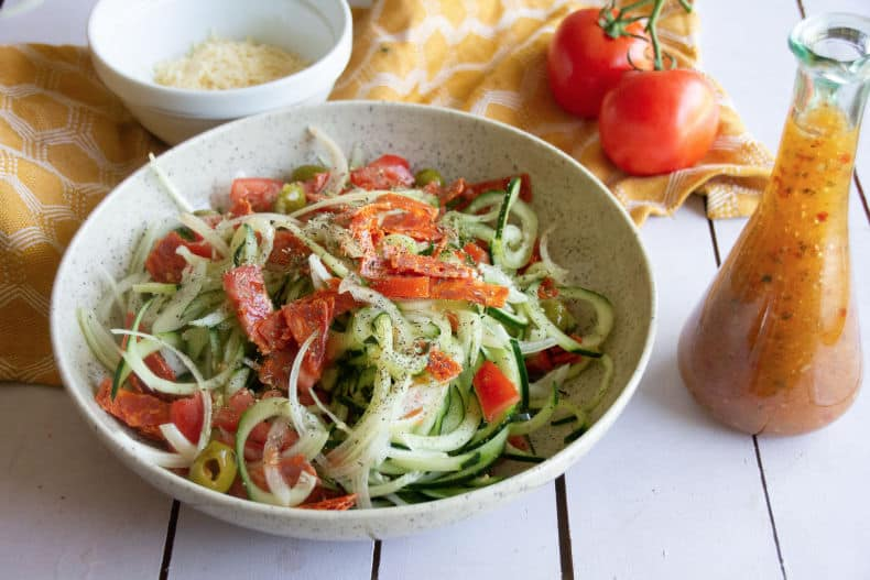 Image of zesty Italian cucumber salad in a speckled bowl on a wood slat table top. Bottle of Italian dressing is beside the bowl, a yellow tea towel, Parmesan and whole tomatoes are in the background