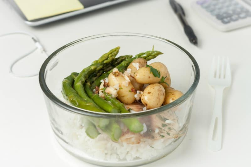 a glass container with lunch with leftovers on a desk at work