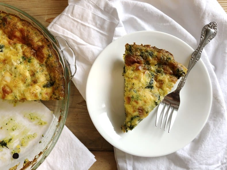 Overhead image of sausage spinach frittata slice on a plate with white napkin and wooden background.