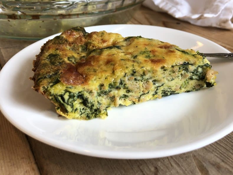 Close-up image of sausage spinach frittata slice on a plate with white napkin and wooden background.