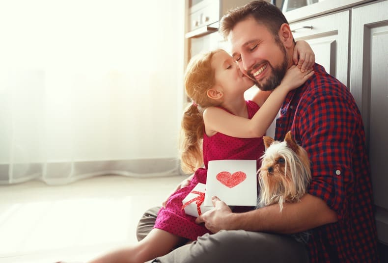 little girl kissing her dad's cheek with a greeting card and gift for dad