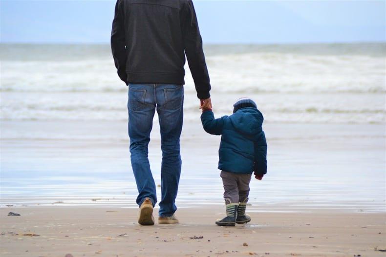 little boy holding dad's hand walking on beach