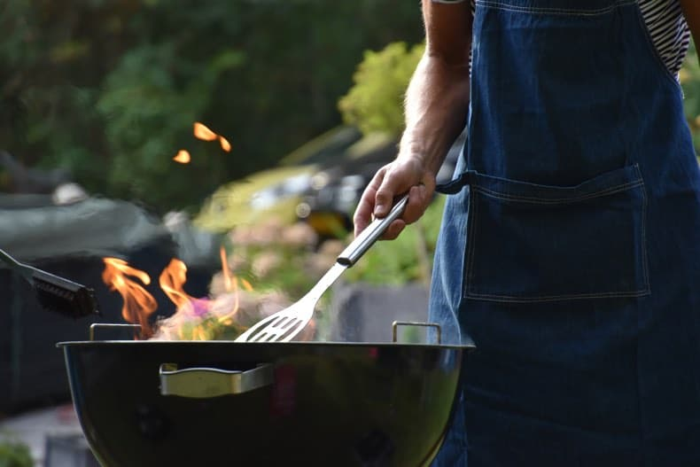 lower half of man cooking meat on a grill to suggest bbq gift ideas for dads