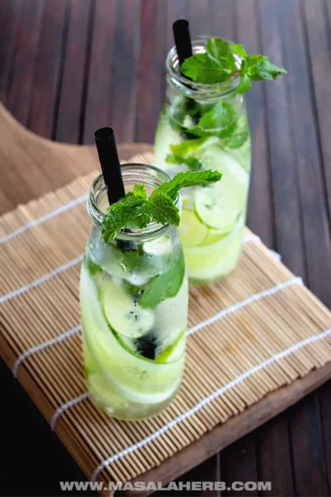 two glasses of cucumber mint water on a bamboo placemat on a wooden surface