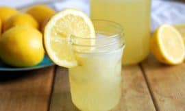 small jar of homemade lemonade with lemons in background