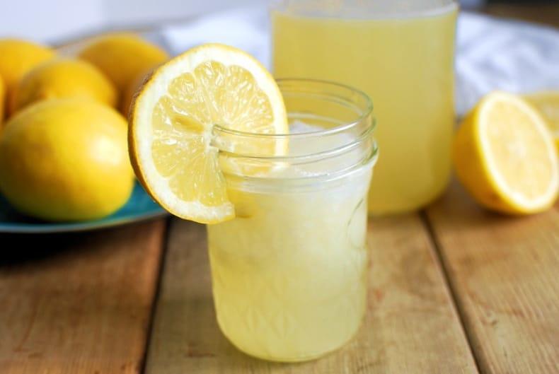 small glass of homemade lemonade with lemon garnish and lemons on a plate
