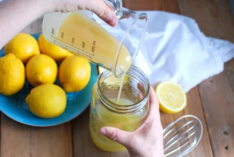 pouring melted honey into a quart jar to make lemonade