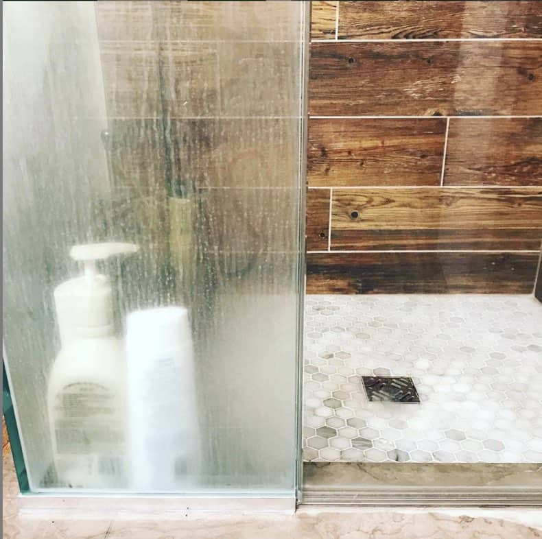 glass shower wall and door half with soap scum, and half cleaned with norwex window cloth