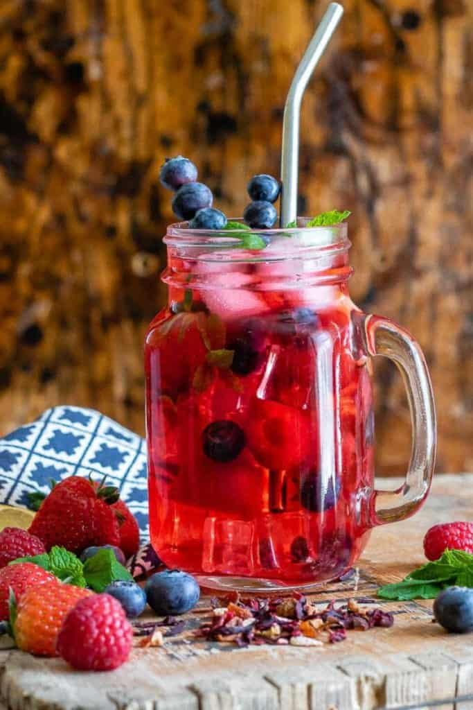glass of iced tea with vibrant red berry color, and blueberries in and around for decoration, on a wooden surface