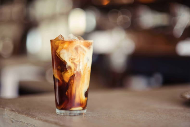 iced coffee with swirling cream in a glass, on a table with blurred background