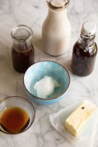 Ingredients for butter chai latte sit in glass bottles, small blue pottery bowl and a glass bowl on a marble counter.