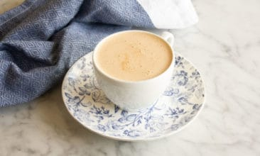 Butter Chai Latte in a white teacup sits on a blue and white saucer on a marble counter. A blue tea towel sits in the background.