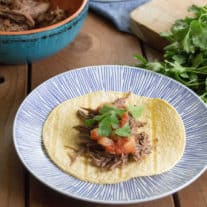 On top of a wooden table sits a blue plate with a tortilla topped with shredded beef, chopped tomatoes and cilantro garnish.