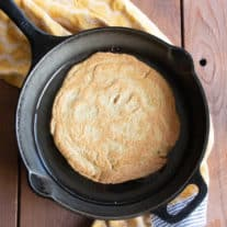 A lentil and chickpea flatbread sits inside a black cast iron pan, resting on a yellow tea towel atop a wooden table surface.