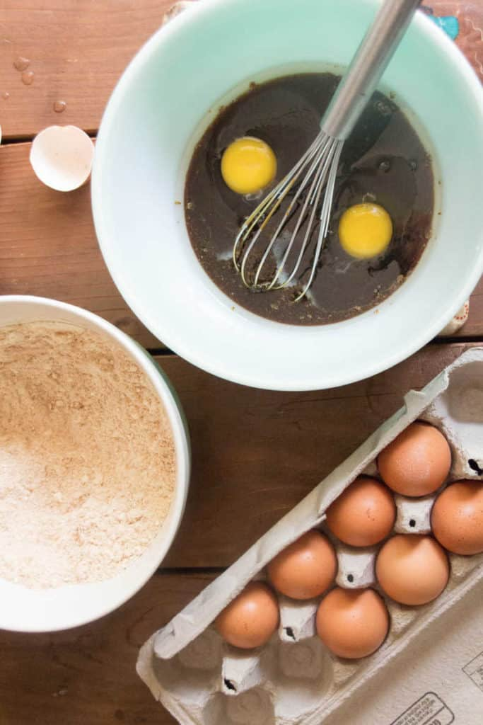 Vanilla extract and eggs have been added to the cooled honey mixture. A bowl of combined dry ingredients and an open egg carton sits nearby.