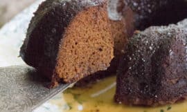 Maple Glazed Gingerbread Bundt cake sits on a white plate with a soft botanical pattern. A piece of cake has been cut and is being lifted with a silver cake slicer.