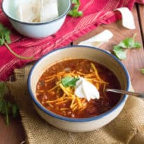 a bowl of chili in a white bowl, sitting on a wood surface, surrounded by a red linen, cilantro, and a bowl of sour cream