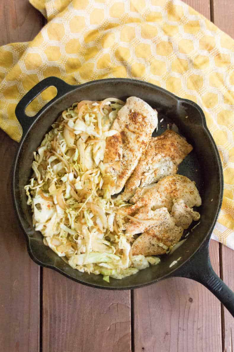 A view from above, a cast iron pan full of smoky cabbage noodles and cooked chicken breasts, sits on a yellow dish towel a top a wood slat table.