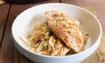 A white bowl with a bed of cabbage noodles and a chicken breast on top.