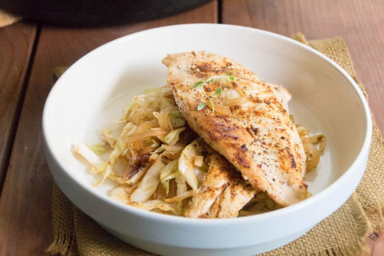 A white bowl with a bed of chicken and cabbage noodles.
