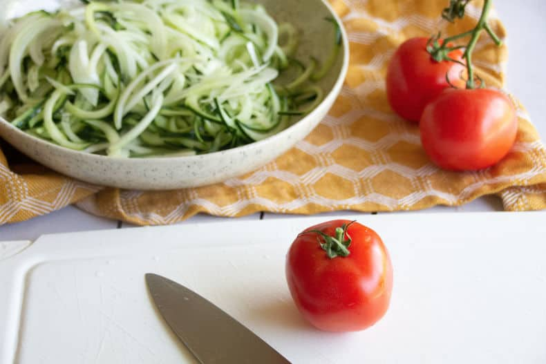 A whole tomatoe sits on a white cutting board with a knife laid next to it. In the background is a white pottery bowl with spiralized cucumbers in it.