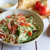 On a white slat table sits a beige pottery bowl with a colourful cucumber, tomato, onion salad mixed in it. A bowl of parmesan cheese, two whole tomatoes, and zesty italian dressing in a glass dressing dispenser sit nearby.