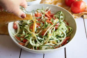 Ingredients for the zesty italian cucumber salad are added to a creamy white pottery bowl while a glass salad dressing bottle is held above and drizzles the italian dressing onto the salad.