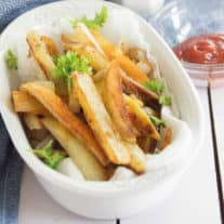 Homemade French Fries sit in a white ceramic bowl on a white wood tabletop with a glass bowl of ketchup, a salt shaker and a blue tea towel in the background.