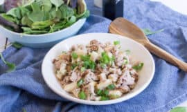 Waldorf Tuna Salad in a white bowl, on top of a blue tea towel. A bowl of baby spinach sits in the background, a wooden spoon sits nearby.