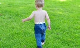 Baby wearing navy and bright blue striped upcycled sweater pants walks on green grass.