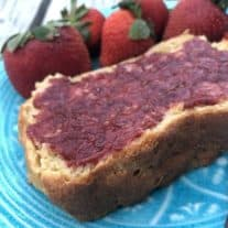 homemade strawberry jam on bread, on a teal plate, with strawberries on the plate