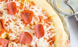 close-up shot of paleo pizza crust with pepperoni and cheese toppings, with a pizza cutter