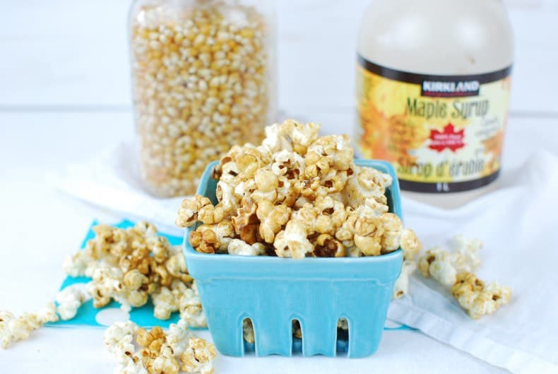 a square ceramic teal basket with homemade stovetop kettle corn spilling out, with a mason jar of popcorn kernels and a jug of real maple syrup in the background