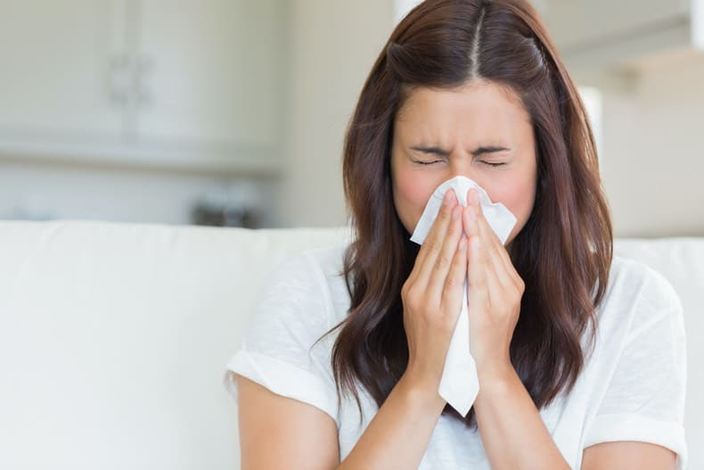 Brunette woman blowing her nose. Article on How to Stop a Cold Virus in Its Tracks.