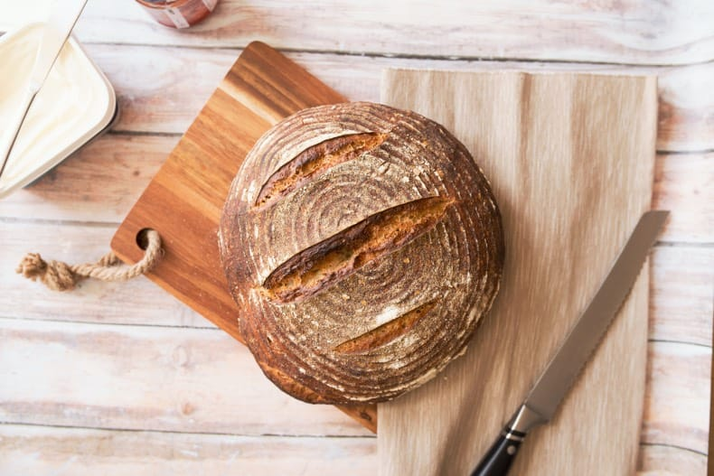 Image is of a loaf of sourdough bread on a cutting board with a knife.