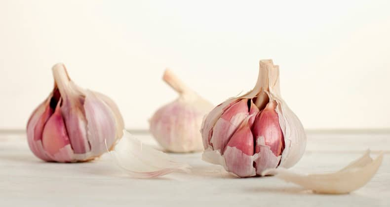 Three heads of garlic on flat surface, partially peeled.