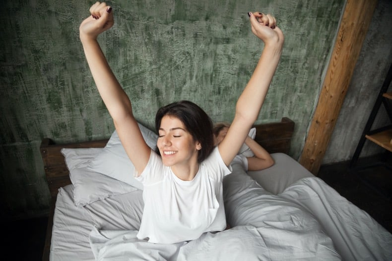 Woman waking up and sitting in bed stretching, looking satisfied after a good sleep.