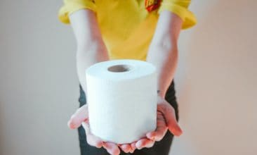 girl holding roll of toilet paper and wearing a yellow shirt