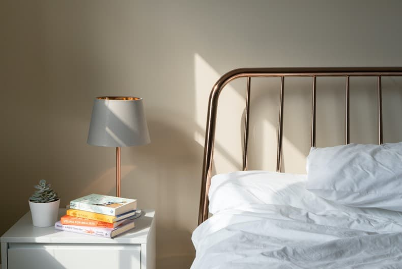 A peaceful bed and nightstand vignette - essential for reducing anxiety at night and getting better sleep