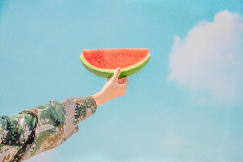 arm holding up a hunk of watermelon against a blue sky