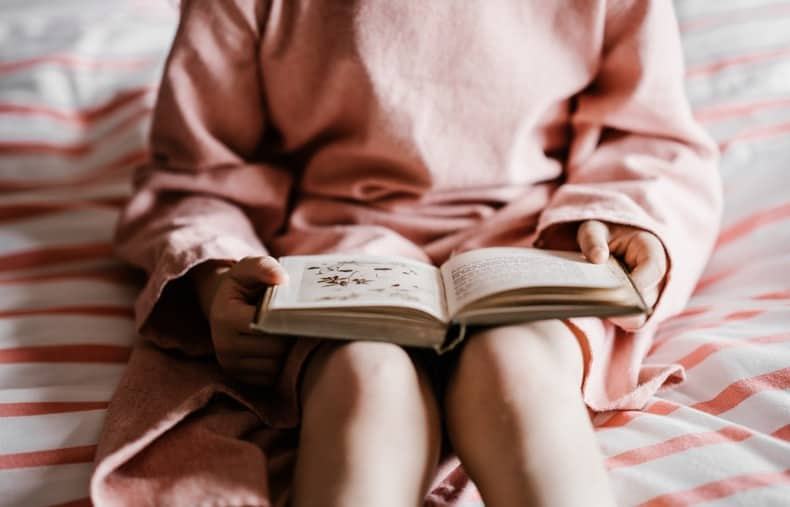 A child sits on a bed reading, with an old vintage nature book sitting open on their lap.