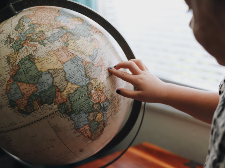 A child is looking at a vintage style globe with their finger pointing to the right of Africa.