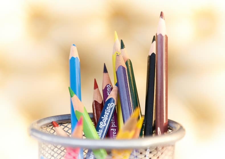 A silver mesh pencil cup filled with sharpened pencil crayons of many different colours.