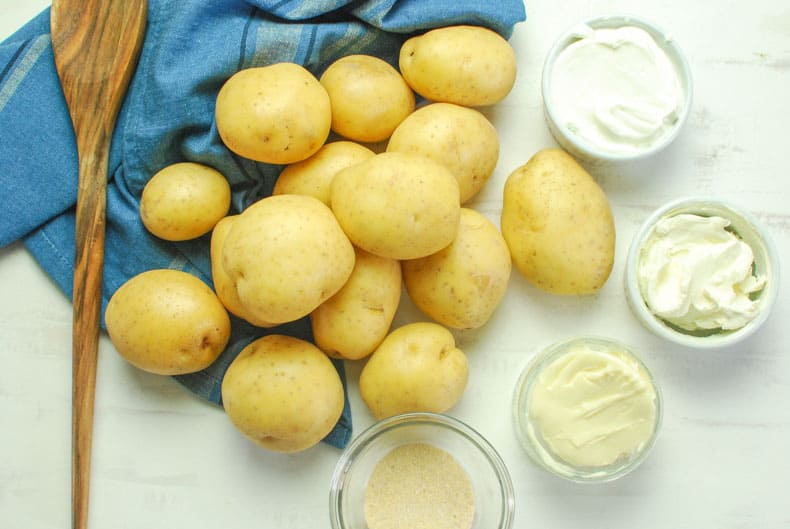 Ingredients for sour cream mashed potatoes with a blue towel and wooden spoon.